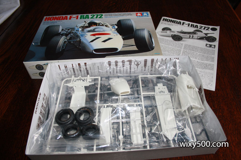The unboxing, all the parts in their bags. My kit has box art of a frontal view painting of the car whereas photos on the web show an alternative box exists that has a rear view photo of the model with the engine cover off.