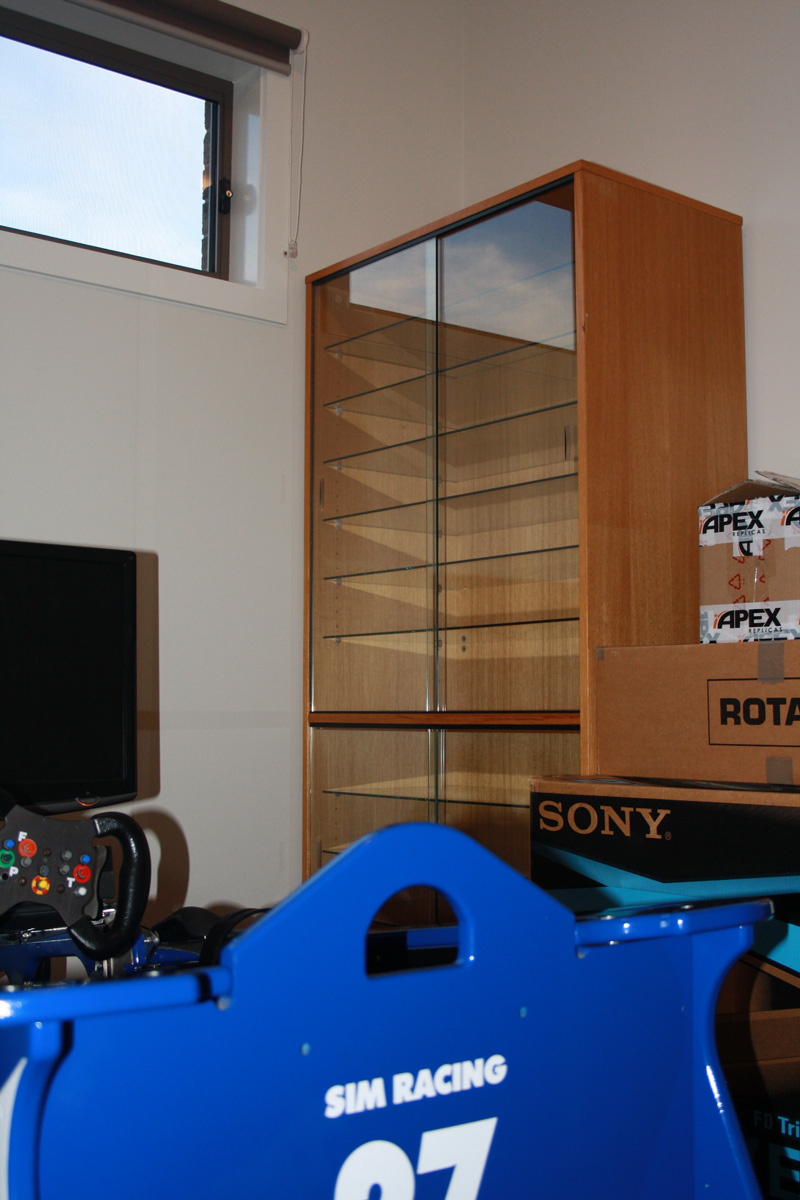 Empty model cabinet and the just-set-up racing simulator in the 'Man Cave'