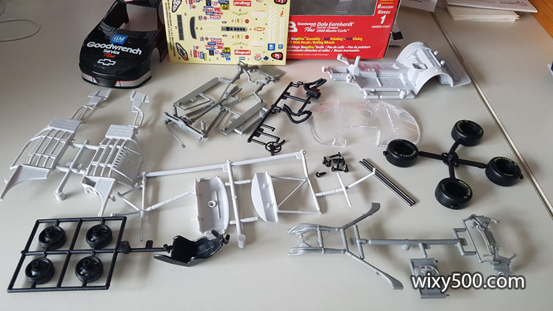 Parts unbagged, molded in black, two shades of grey and clear. Axles are metal, tyres are rubber (with pre-printed sidewalls), markings are adhesive stickers, not waterslide decals.